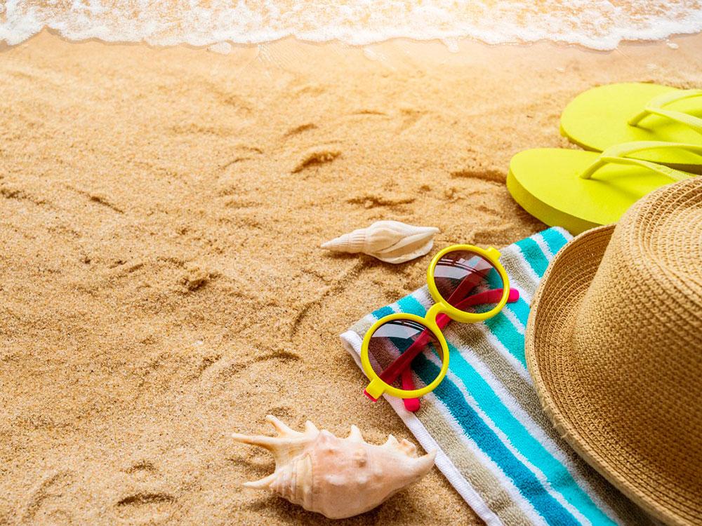 Пляжное полотенце, шляпа, солнечные очки на песке у моря